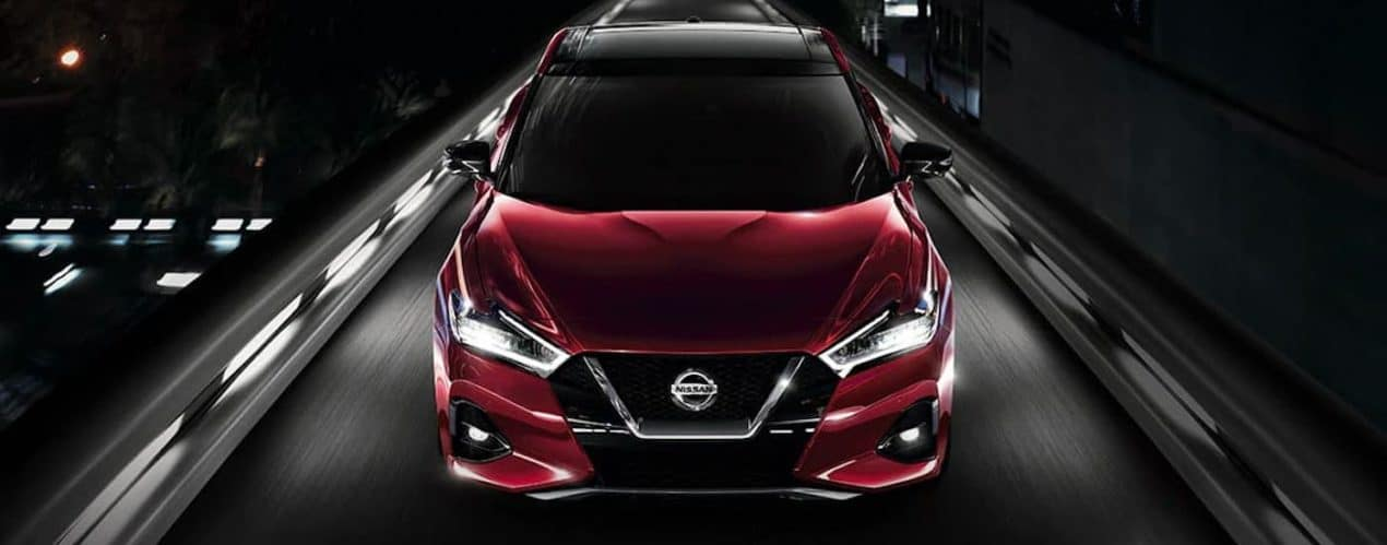 A red 2021 Nissan Maxima is shown from the front driving on a city highway at night.