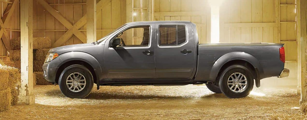 A grey 2021 Nissan Frontier is shown from the side in a hay barn.