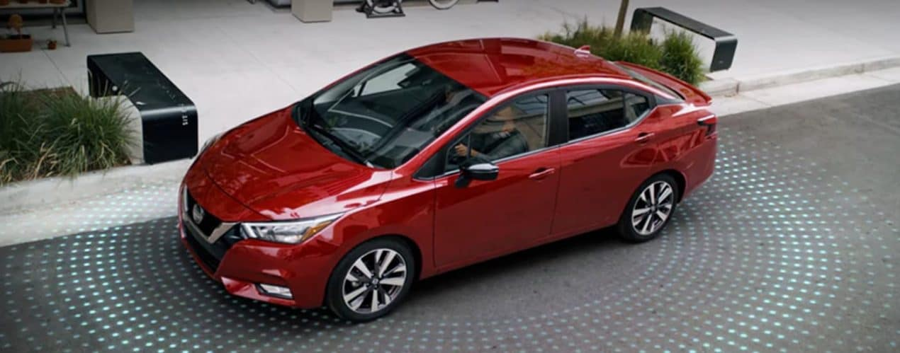 A red 2021 Nissan versa is parallel parking with a light indicators simulated on the ground.