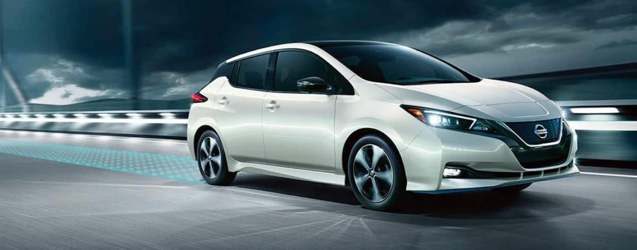 A white 2021 Nissan LEAF is driving on a bridge with simulated safety features coming from the back.