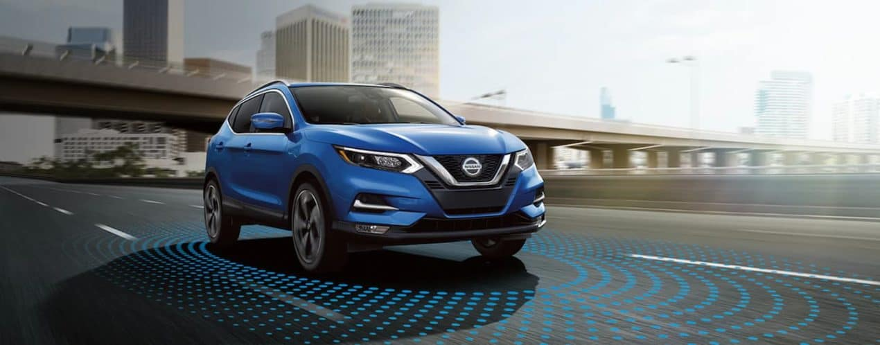 A blue 2021 Nissan Rogue Sport is driving on a highway past a city with simulated blue dots on the road.