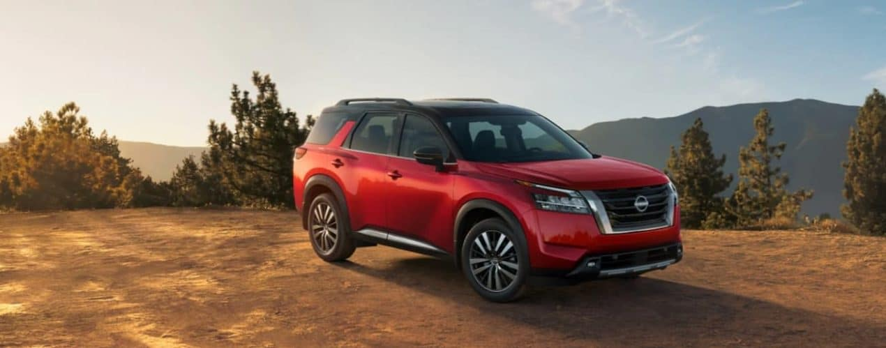 A red 2022 Nissan Pathfinder is parked on dirt with a mountain view at sunset.
