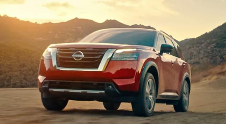 A red 2022 Nissan Pathfinder is driving on a desert road at sunset.