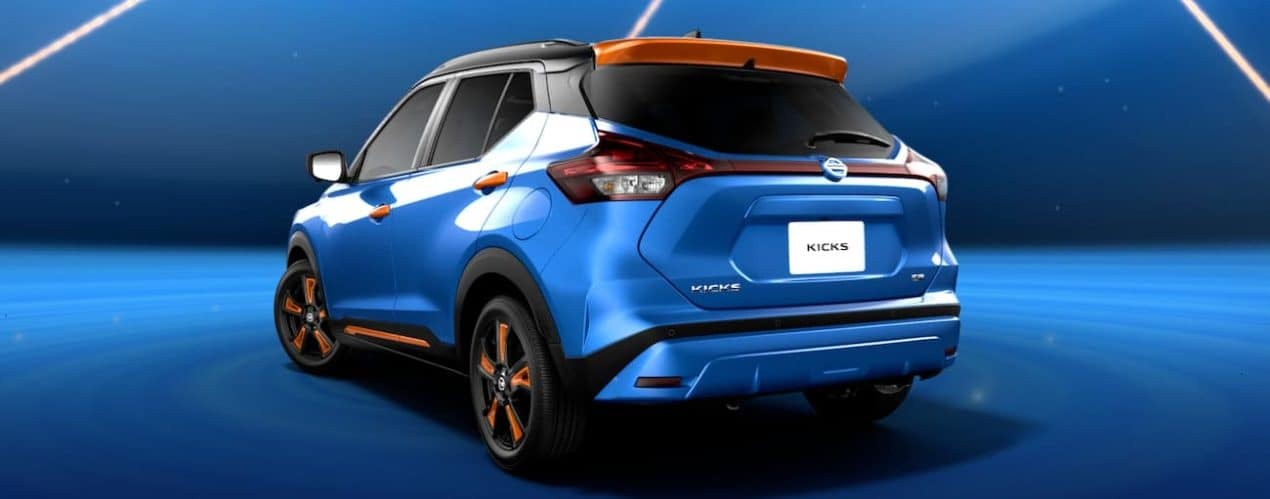 A blue and orange 2021 Nissan Kicks is shown from the rear in front of a blue background.