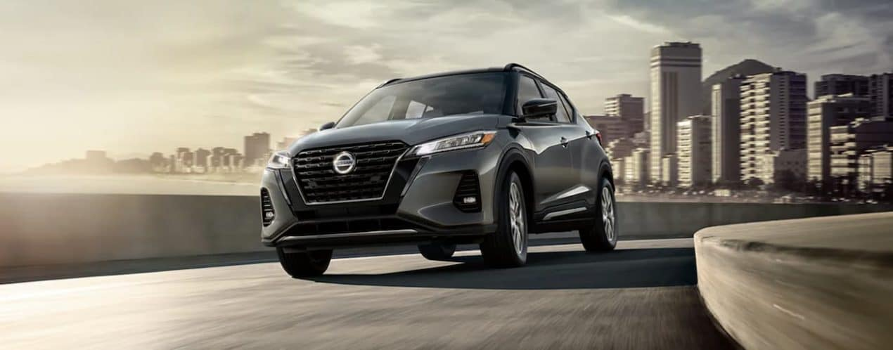 A grey 2021 Nissan Kicks is driving away from a city.
