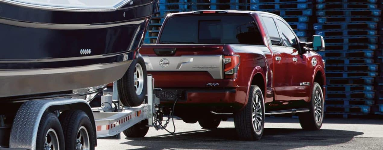 A red 2021 Nissan Titan XD is shown from the rear towing a boat.
