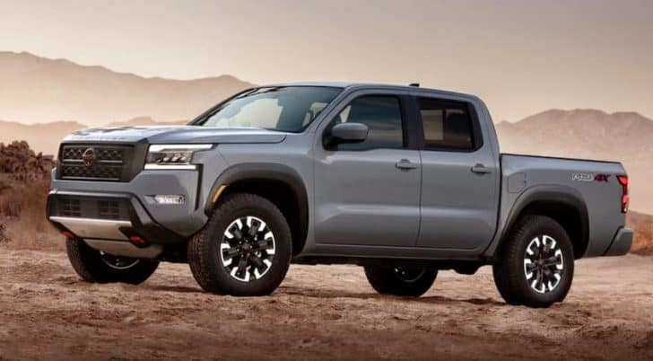 A grey 2022 Nissan Frontier is shown from the side in a desert.