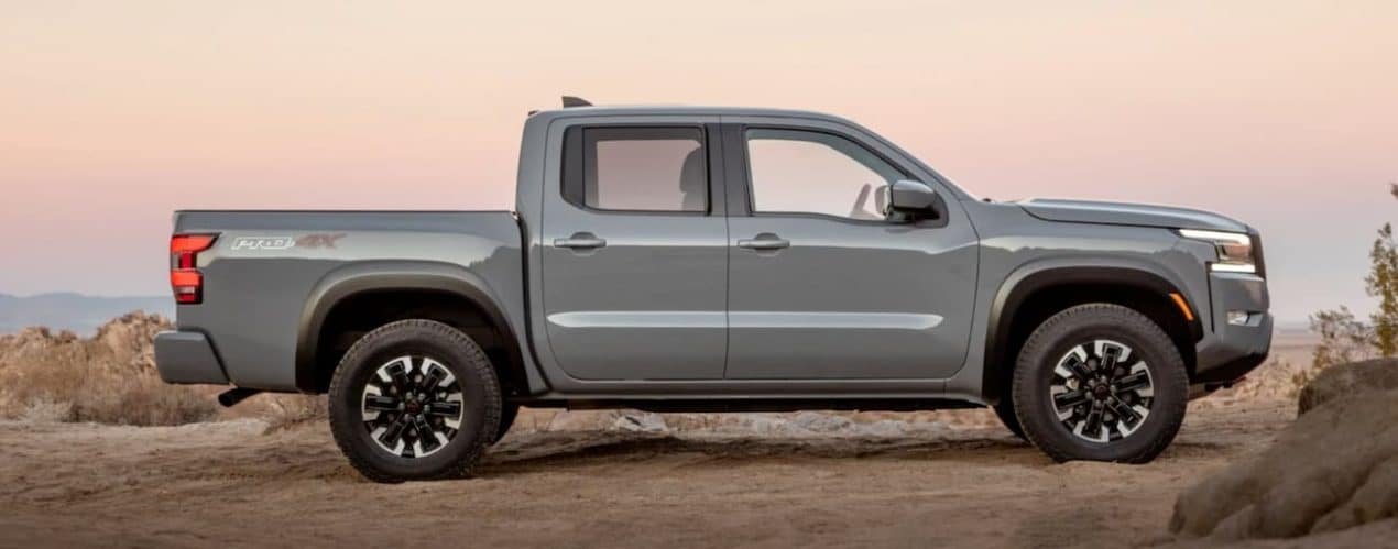 A grey 2022 Nissan Frontier is shown from the side in a desert at sunset.