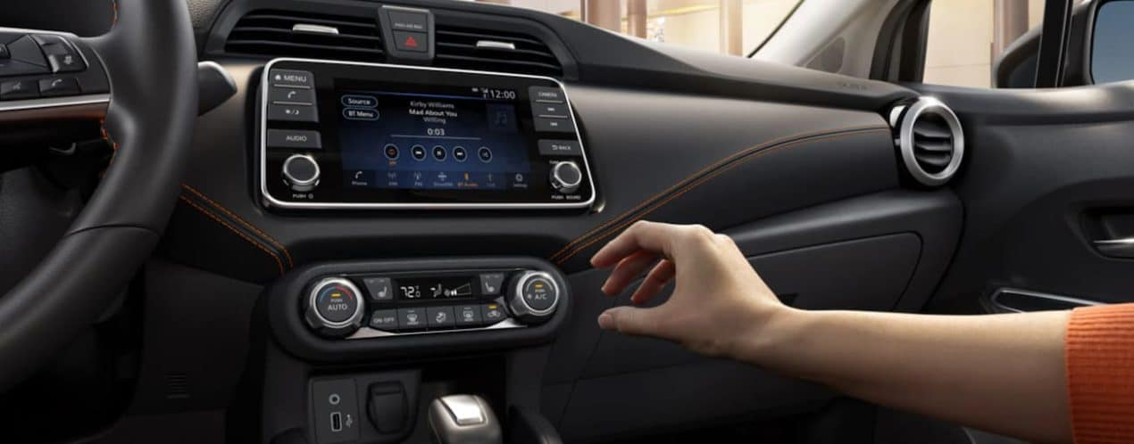 A hand is reaching for the dial on the infotainment screen in a 2021 Nissan Versa.