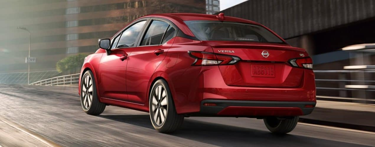 A red 2021 Nissan Versa is shwon from the rear on a city street.