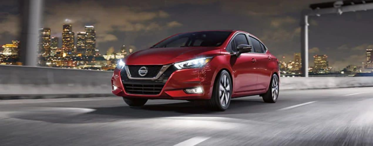 A red 2021 Nissan Versa is driving on a city highway at night after winning the 2021 Nissan Versa vs 2021 Hyundai Accent comparison.